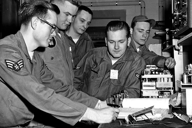 Black and white historical image of 115th Fighter Wing members looking at a piece of equipment