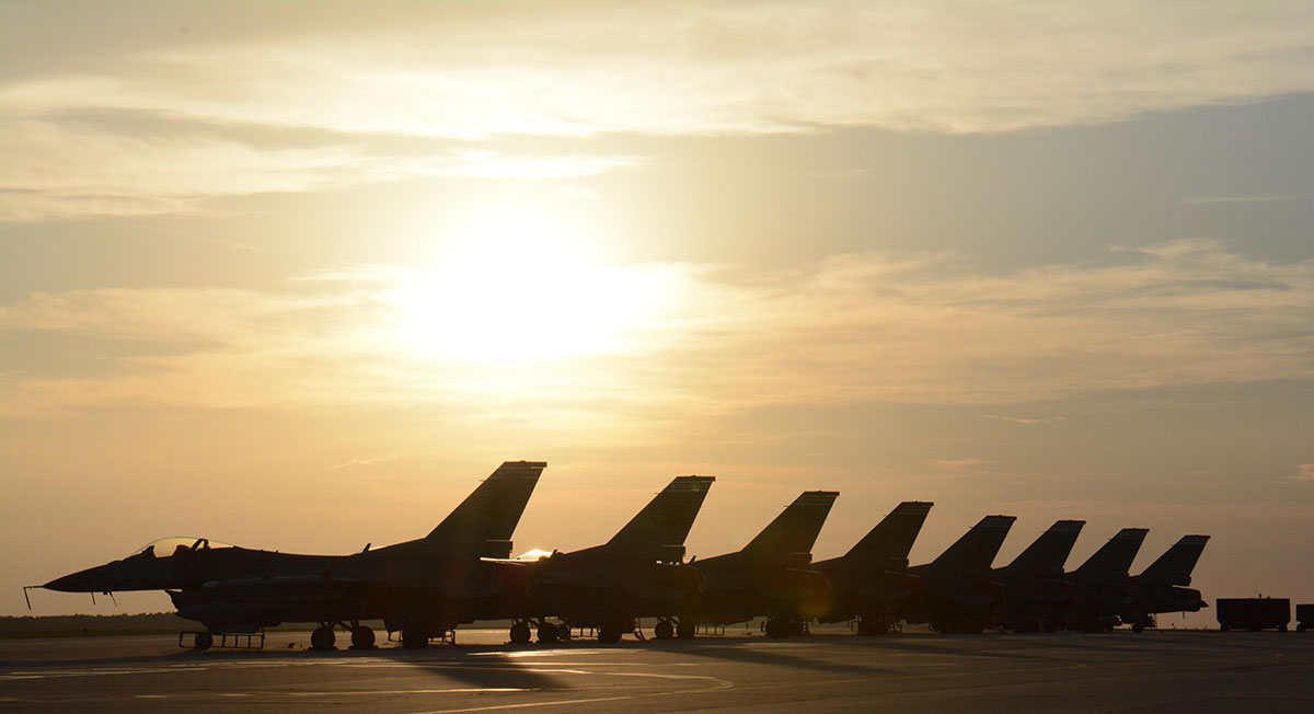 Row of F-35s jets with sun setting in the background